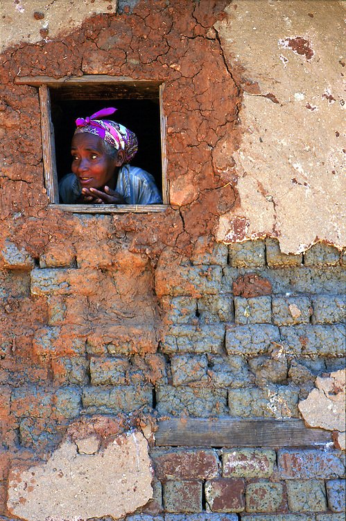 A local woman peers from her mud hut in the Fianarantsua highlands. Poverty is rife in the Fianarantsua Highlands of Madagascar