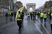 December, 8th, 2018 - Paris, Ile-de-France, France: Demonstrator with yellow peace flag, Arc de Triomphe behind, on Champs Elysees. The French 'Gilets Jaunes' demonstrate a fourth day. Their movement was born against French President Macron's high fuel increases. They have been joined en mass by students and trade unionists unhappy with Macron's policies. Nigel Dickinson