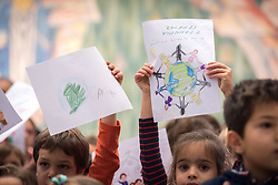 "21 November 2018, Geneva, Switzerland: Children from the Greek schools in Geneva and Lausanne hold up drawings to be given to the Ecumenical Patriarch Bartholomew as a gesture of welcome, as he arrives at the Ecumenical Centre. On the occasion of 2018 World Children's Day, and in recognition of the World Council of Churches' 70th anniversary, UNICEF and WCC convene a number of WCC member churches and common partners to celebrate the UNICEF-WCC global partnership and to take stock of the many achievements of the Churches' Commitments to Children. In line with the spirit of a day ""for children, by children,"" the celebratory event placed children at the centre by asking them to share their recent experiences as participants in the several Youth Talks on ending violence in schools that WCC member churches around the world have organized in recent years; hearing the perspective of young migrants supported by a church-run sponsorship project; and showcasing promising examples of how churches support children in climate justice activities."