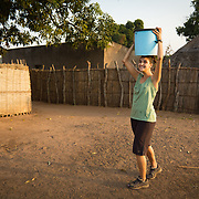 Peace Corps volunteer Rachael demonstrates that she's mastered the technique of carrying a headload of water. Koumbadiouma, Kolda, Senegal.
