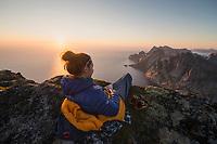 Female hiker relaxes in evening sun on summit of Storskiva, Moskenesøy, Lofoten Islands, Norway