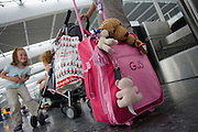 Children experiencing pre-holiday excitement in BA check-in areas at Heathrow Airport's Terminal 5.
