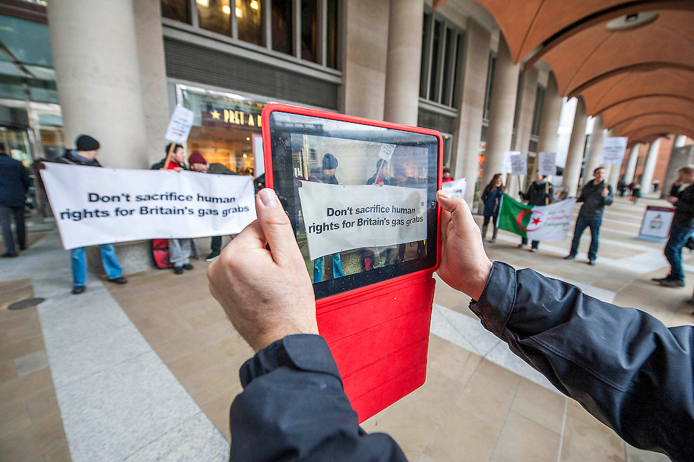 """Spreading the message using new media - i-pad to Youtube. Human rights protestors from the Algeria Solidarity Campaign (ASC) gather outside the London Stock Exchange to raise awareness about what they call 'the repressive Algerian regime' and its links with powerful multinationals such as BP who are keen on its gas reserves. Inside there is a business conference – The Algerian Investor Window – and the protestors hope to highlight issues about """"British collusion with a repressive and corrupt regime for the sake of business interests and securing fossil fuel supplies"""" with the attendees. Paternoster Square, London, UK 10 Feb 2014. Guy Bell, 07771 786236, guy@gbphotos.com"""