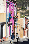 Two women walk together holding hands past the brightly painted pink Hotel Centenario Centro in the beautiful colonial village of Bernal, Queretaro, Mexico. Bernal is a quaint colonial town known for the Pena de Bernal, a giant monolith which dominates the tiny village is the third highest on the planet.