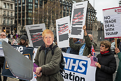 London, UK. 25 November, 2019. An activist wearing a Boris Johnson mask prepares to carve up the NHS during a protest by campaigners from Keep Our NHS Public, Health Campaigns Together, We Own It and Global Justice Now in Parliament Square to call on Prime Minister Boris Johnson to end privatisation of healthcare in the National Health Service (NHS).