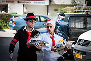 """Orthodox couple in Purim costume with Mishloach manot. Photographed in Bnei Brak, Israel. Mishloach manot (literally, """"sending of portions"""") also called a Purim basket, are gifts of food or drink that are sent to acquaintances on Purim day"""
