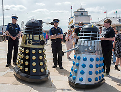 © Licensed to London News Pictures; 30/05/2021; Weston-super-Marel, UK. Four Daleks, organised by Ian and Tracy McTeague, patrol the promenade interacting with the public and two PCSOs on the late May bank holiday weekend during the covid coronavirus pandemic as restrictions have been eased to allow travel and staycations in England and Wales. The weather is forecast for this weekend to have the hottest day of the year so far. Photo credit: Simon Chapman/LNP.