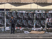 Man in front of a poster wall in Nolita, New York City.