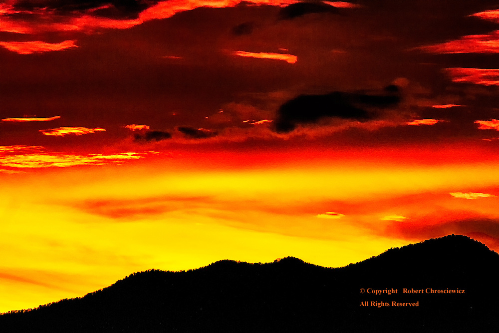 Sunrise-Lovina Bali: A dramatic red-yellow sky announces the morning, with the foreground hillside silhouetted, Lovina Bali Indonesia.