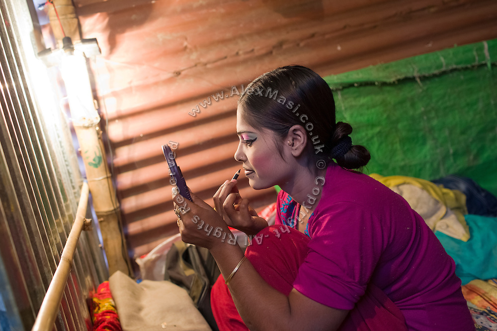 A young woman is applying makeup before performing at one of the regular night dance shows being set up during the yearly Sonepur Mela, Asia's largest cattle market, in Bihar, India.