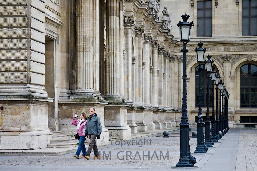 Couple stroll past a row of street lights by The Louvre Museum, Paris, France
