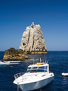 High Peak Rocks with a boat in the foreground. View of Poor Knights Islands, summer, Northland, New Zealand