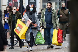 © Licensed to London News Pictures. 04/11/2020. Manchester, UK. Shoppers carry lots of shopping bags as they walk down a busy Market Street in Manchester on the last day before national lockdown.. Photo credit: Kerry Elsworth/LNP