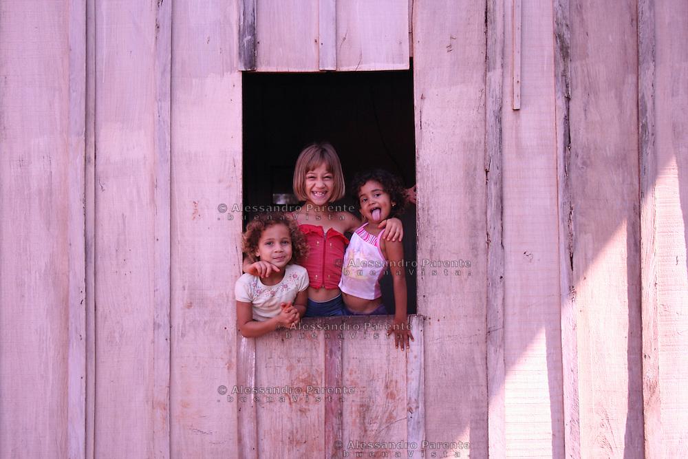 Three little girls smiling on a window in Brazil.