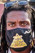 "15 AUGUST 2020 - MINNEAPOLIS, MINNESOTA: A member of MN Freedom Fighters, who provide security at the George Floyd Memorial in Minneapolis. Floyd, an unarmed Black man, was killed by Minneapolis police officers of May 25 in front of Cup Foods, a convenience store at the intersection of 38th and Chicago Ave. His killing sparked a week of violent protests across the country. The intersection where he was killed is still closed and has become an unofficial memorial visited by hundreds of people every day. Saturday, more than 100 people gathered at the memorial to demand the city preserve the memorial. On Saturdays in August, the intersection has a market, with venders selling Afro-centric merchandise. The city of Minneapolis had planned to start reopening the intersection as soon as Monday Aug. 17, but delayed those plans indefinitely on Friday, Aug. 14. City residents have created a ""George Floyd Zone"" at the intersection. They're demanding the recall of Hennepin County Attorney Mike Freeman, requiring Minneapolis police officers have their own private liability insurance, and the allocation of funds for businesses and residents in the community. The city is considering officially renaming Chicago Ave. between 37th and 39th ""George Floyd Jr. Place.""     PHOTO BY JACK KURTZ"