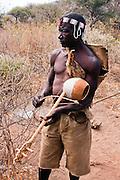 A Hadza hunter wearing raditional colorful beads headband, plays a rebab a single-string bowed lute. Photographed in Lake Eyasi,  Tanzania