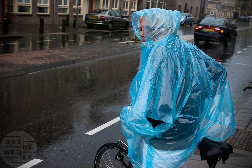 Een vrouw op de fiets wacht met een stuk regenponcho in haar mond in de stromende regen tot ze over kan steken.<br /> <br /> A woman on a bike is waiting in the rain to cross the street.
