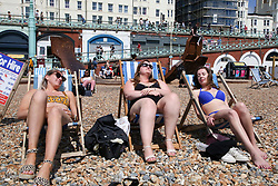 © Licensed to London News Pictures. 30/05/2021. Brighton, UK. Three friends from London enjoy the warm sunshine on the Brighton seafront on the hottest day of the year so far. According to the Met Office, a high of 24 degrees celsius is forecast for the bank holiday weekend, after weeks of rain in the South East of England. <br /> Photo credit: Dinendra Haria/LNP