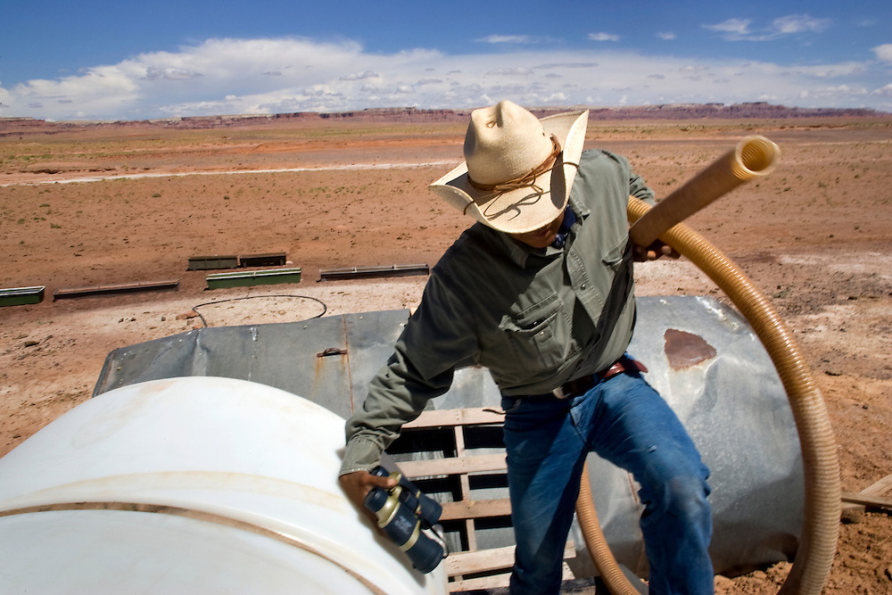 """Raymond Knight works in the Grand Canyon during the week, helping with mule trains carrying supplies. On weekends, he hooks a trailer to his pick-up and carries water to family and friends. On one recent weekend, he ferried the tank back and forth between a ranch, where people had gathered to brand cattle.  """"They use it up pretty fast,"""" he said. . Water haulers haul because the Navajo Nation lacks adequate, clean water and the infrastructure to deliver it. The reservation lies between three major rivers — the San Juan, the Colorado and the Little Colorado — but the tribe still relies mostly on groundwater. Drilling a well is easier and cheaper than building a pipeline.  Not all the wells produce usable water. Many dry up in a drought. Windmills break down, often for weeks at a time. As a result it's not uncommon for people to drive 30 miles or more to find water."""
