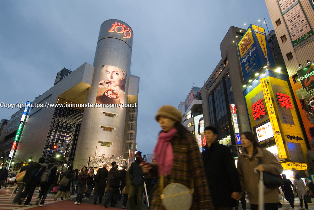 Pedestrians crossing busy street intersection at night in Shibuya Tokyo Japan