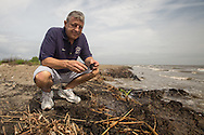 April 9, 2015, Almost five years after the BP oil spill,  Dean Blanchard owner of Dean Blanchard Seafood, stand on a tar matt on East Grande Terre, a barrier island in Plaquemines Parish that was hit hard by the BP oil spill in 2010.BP recently led an effort to clean up a tar mat uncovered on the same area of the beach a couple weeks before that was connected to the BP oil spill.