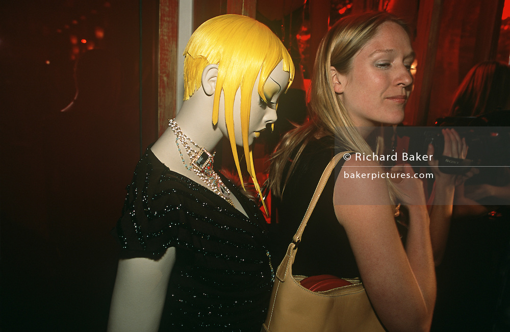 A party girl stands in front of a fashion mannequin at a couture launch event. The gathering was to celebrate the opening of the company's new store on the Fulham Road in a trendy area of Chelsea.