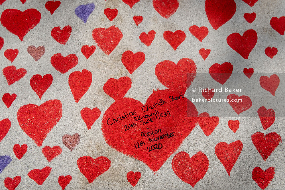 A detail of red hearts on the wall that forms the National Covid Memorial Wall, a tribute to the 150,000-plus British victims of the Coronavirus pandemic. Christine Elizabeth Short is mentioned as succumbing in November 2020. Bereaved family and friends of Covid-19 victims have started working on the wall located outside St Thomas' Hospital, and which faces the Houses of Parliament in Westminster, on 30th March 2021, in London, England. Prime Minister Boris Johnson was treated for Covid at St Thomas' last year.