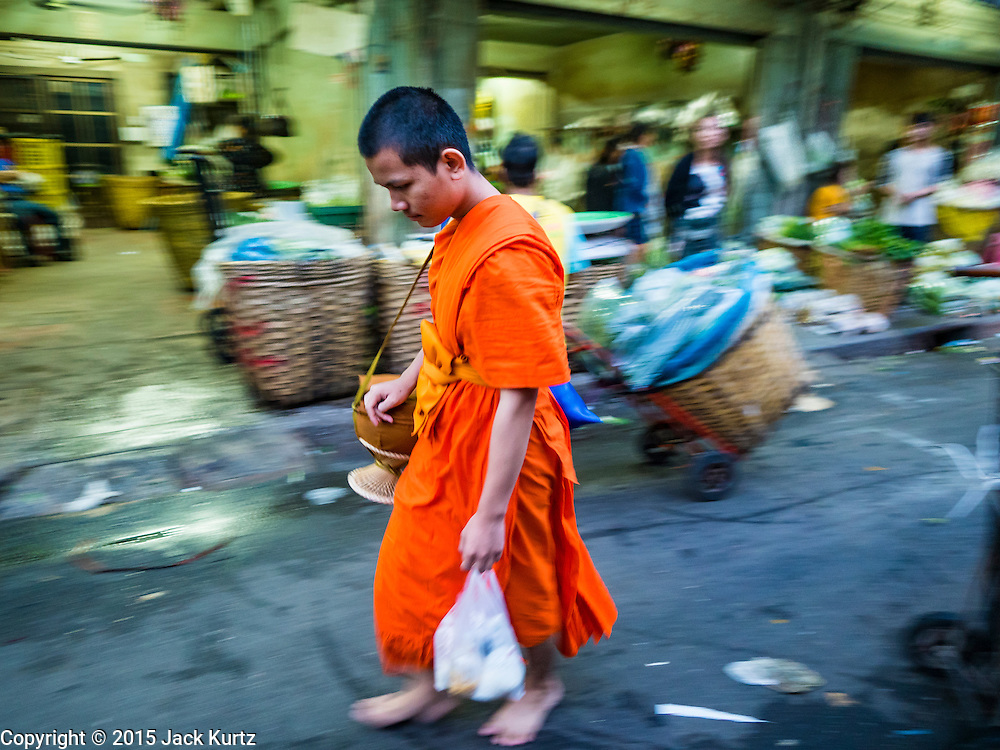 """21 DECEMBER 2015 - BANGKOK, THAILAND: A Buddhist monk walks through Pak Khlong Talat, also called the Flower Market. The market has been a Bangkok landmark for more than 50 years and is the largest wholesale flower market in Bangkok. A recent renovation resulted in many stalls being closed to make room for chain restaurants to attract tourists. Now Bangkok city officials are threatening to evict sidewalk vendors who line the outside of the market. Evicting the sidewalk vendors is a part of a citywide effort to """"clean up"""" Bangkok.       PHOTO BY JACK KURTZ"""