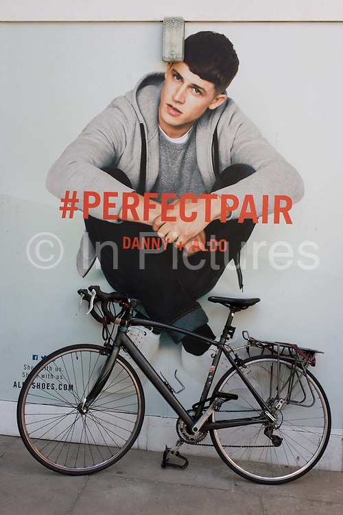 Male model seemingly sitting on a bicycle in central London. As a scene of humour and misinterpretation, we see the funny said eof fashion and advertising - the juxtaposition of male beauty and the nature of a parked bike: the random positioning of the ad with the everyday. The #PERFECTPAIR hashtag comes from the Aldo shoe brand.