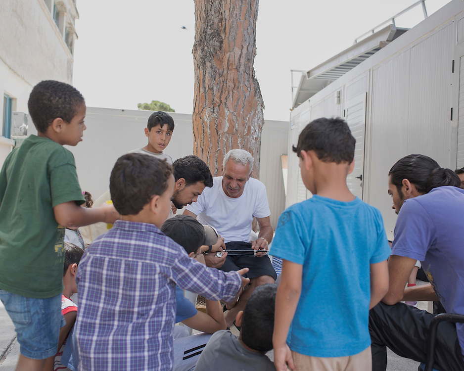 Syrian refugee children gather around a man repairing a fishing rod in the gounds of PIKPA, a refuge opened in January 2016 by the Leros Solidarity Network as a shelter for families and unaccompanied minors.