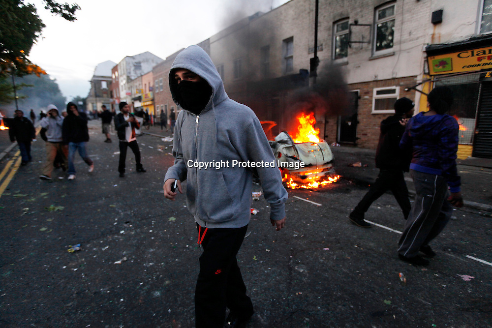 Rioters walk in front of a burning car in Hackney, North London, Britain, 08 August 2011, during the third day of violence in which Police have clashed with rioters in Hackney and vehicles have been set on fire in Peckham and Lewisham. This follows two nights of violence over the weekend after the police shooting of a man in Tottenham. More than 200 people have been arrested and 35 police officers injured.<br /> Violence erupted in reaction to a fatal shooting incident in Tottenham, in which a policeman was injured on 04 August and a local 29-year-old man named as Mark Duggan killed by armed officers.  EPA/KERIM OKTEN