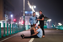 © Licensed to London News Pictures . 26/09/2017. Brighton, UK. A couple sit together on the pavement on Brighton Promenade . Revellers at the end of a night out during Freshers week , when university students traditionally enjoy the bars and clubs during their first nights out in a new city . Photo credit: Joel Goodman/LNP