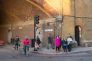 People under the railway arches at Bermondsey Street in Southwark, London, UK.