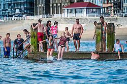 Aberystwyth, Wales UK, Friday 25 July 2014<br /> <br /> Groups of teenagers in the first week of the long summer holidays enjoying the continuing hot sunny weather jumping and diving off the wooden jetty at the seaside in Aberystwyth on the west wales coast UK. <br /> <br /> Behind them is the newly restored Grade II listed public shelter, severly damaged in the winter storms<br /> <br /> Todays peak temperature is forecast to be around 25c, a few degrees cooler than recent days but still above the average for this time of year. Inland the peak may reach nearer 30c in places<br /> <br /> photo © keith morris