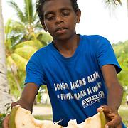 Boy preparing young coconut.