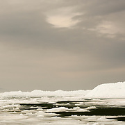 An Bald Eagle Sits Atop A Pile Of Ice In The Straits Of Mackinac With The Mackinac Bridge In The Background