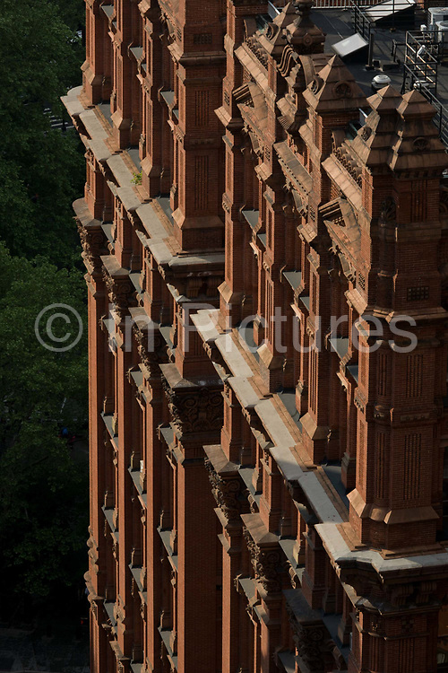 Red brick apartment building in Manhattan, New York City. A detail of ledges are seen from a high angle as we look down from a higher building.