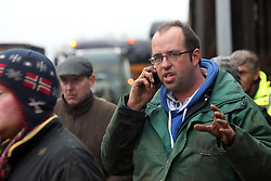 © Licensed to London News Pictures. Moorland. Somerset. 06/02/14. Owner of farm James Winslade (portrait) green top on phone. West Yeo farm - The evacuation of 550 beef cattle all in a day. Rebecca Horsington put out an appeal on Facebook for help today - about 30 farmers arrived with trailers to take cattle to a nearby cattle market in Bridgwater out of danger. from floodwater which was rising rapidly.. Photo credit : Jason Bryant/LNP