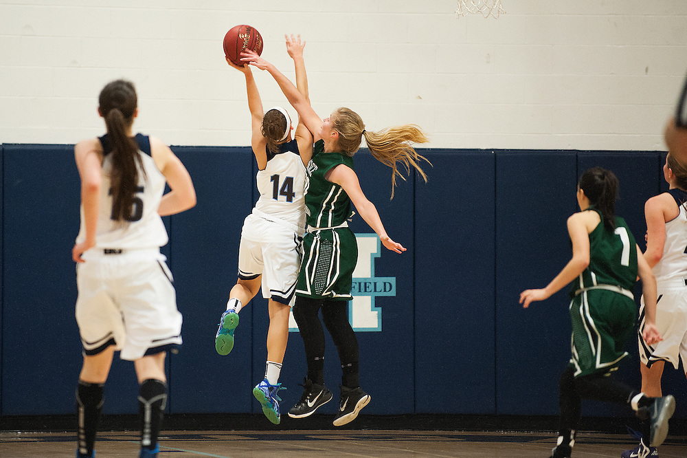 Rice forward Stephanie Langlais (10) tries to block the shot by Mount Mansfield forward Katie Estes (14) during the girls basketball game between the Rice Green knights and the Mount Mansfield Cougars at MMU High School on Friday night December 4, 2015 in Jericho. (BRIAN JENKINS/for the FREE PRESS)