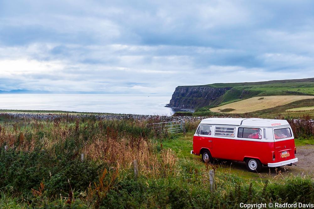 VW bus camper overlooks the ocean on Isle of Skye, Scotland