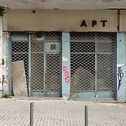 """An abandoned shop in 12 Apostolon Sq , Thessaloniki. The sign reads """"art""""."""
