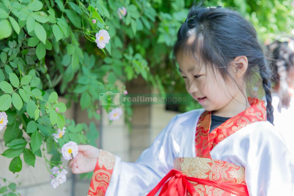 April 28, 2018 - Rugao, Rugao, China - Rugao, CHINA-28th April 2018: Kids wearing traditional Chinese clothes enjoy blooming roses in Rugao, east China's Jiangsu Province. (Credit Image: © SIPA Asia via ZUMA Wire)