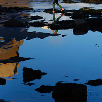A young surfer heads to the beach at low tide after a session at Santa Cruz, California's world renowned surf break Steamer Lane.<br /> Photo by Shmuel Thaler <br /> shmuel_thaler@yahoo.com www.shmuelthaler.com