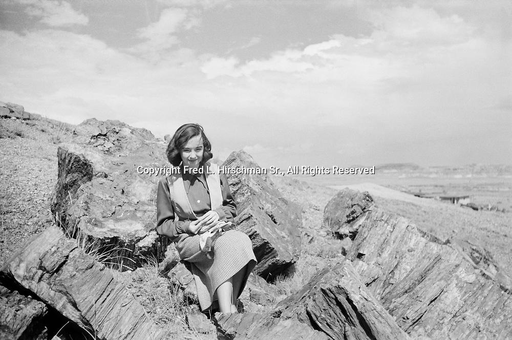 Octavia Hirschman sittingamong petrified logs, Rainbow Forest, Petrified Forest National Park, Arizona (September 1949)