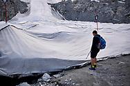 Un escursionista vicino ai teloni di copertura del Ghiacciaio del Presena. Trentino, Agosto 2020.
