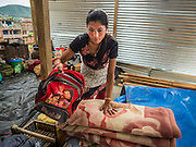 02 AUGUST 2015 - BHAKTAPUR, NEPAL:  A woman sets up her family's living space in a small Internal Displaced Person (IDP) camp at Durbar Square in Bhaktapur for people left homeless by the Nepal earthquake. The Nepal Earthquake on April 25, 2015, (also known as the Gorkha earthquake) killed more than 9,000 people and injured more than 23,000. It had a magnitude of 7.8. The epicenter was east of the district of Lamjung, and its hypocenter was at a depth of approximately 15km (9.3mi). It was the worst natural disaster to strike Nepal since the 1934 Nepal–Bihar earthquake. The earthquake triggered an avalanche on Mount Everest, killing at least 19. The earthquake also set off an avalanche in the Langtang valley, where 250 people were reported missing. Hundreds of thousands of people were made homeless with entire villages flattened across many districts of the country. Centuries-old buildings were destroyed at UNESCO World Heritage sites in the Kathmandu Valley, including some at the Kathmandu Durbar Square, the Patan Durbar Squar, the Bhaktapur Durbar Square, the Changu Narayan Temple and the Swayambhunath Stupa. Geophysicists and other experts had warned for decades that Nepal was vulnerable to a deadly earthquake, particularly because of its geology, urbanization, and architecture.      PHOTO BY JACK KURTZ