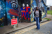 Street art depicting the Kray twins as Superman and Spiderman in Shoreditch, London, UK. Reggie and Ronnie Kray were legendary East End gansters in the 1960s and in many minds still regarded as heroes as opposed to superheroes by some locals. Others despise the idea of the gangster culture, and subsequently the faces of the Krays in this grafitti were defaced.