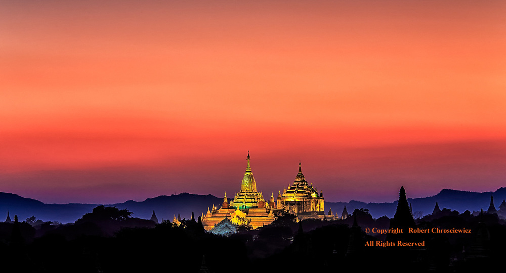 The Ananda and Thatbyinnyu Temples are captured in spotlights as the sun sets and paints the sky a rainbow of colours, Bagan Myanmar.