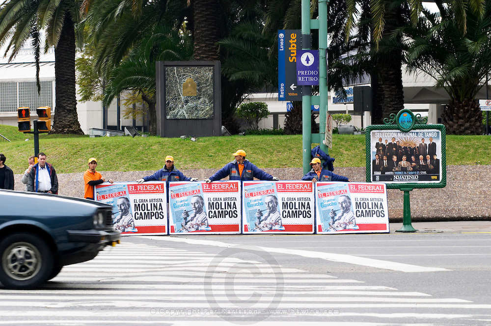 A pedestrian crossing on a street, four persons carrying publicity boards that are held up and shown to the drivers in the cars, a kind of manual movable advertising on the street. Buenos Aires Argentina, South America