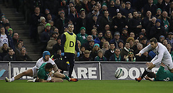 England's Elliot Daly scores a try after a mistake by Ireland's Jacob Stockdale during the Guinness Six Nations match at the Aviva Stadium, Dublin.